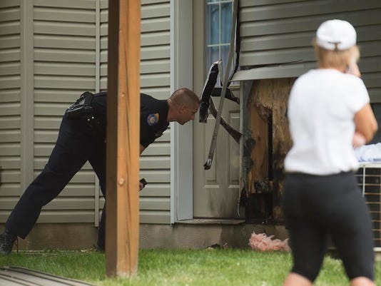 A firefighter looks at damage to Penn Township home on Wednesday.