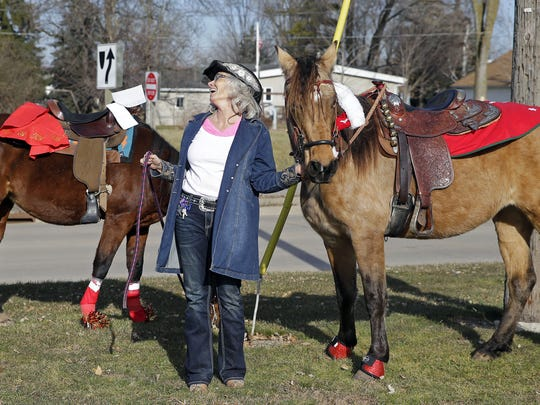 LeAnn Santiago keeps watch on two horses before a group of riders goes Christmas caroling in Fox Crossing.