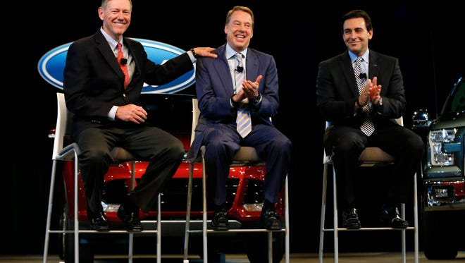 Ford Motor CEO Alan Mulally, left, celebrates with Executive Chairman Bill Ford Jr., and Chief Operating Officer Mark Fields while announcing that Mulally retires July 1 and Fields will replace him.