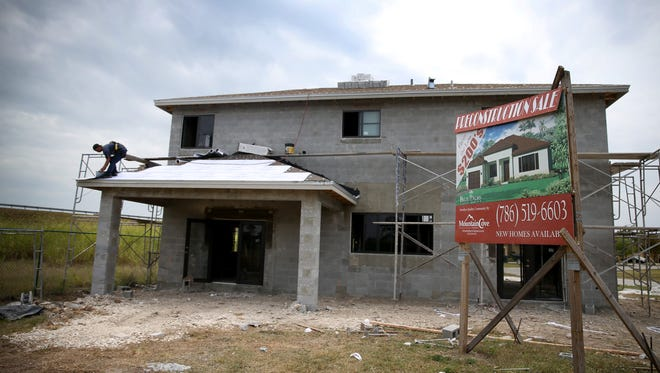 A construction worker works on a new single family home in Miami.