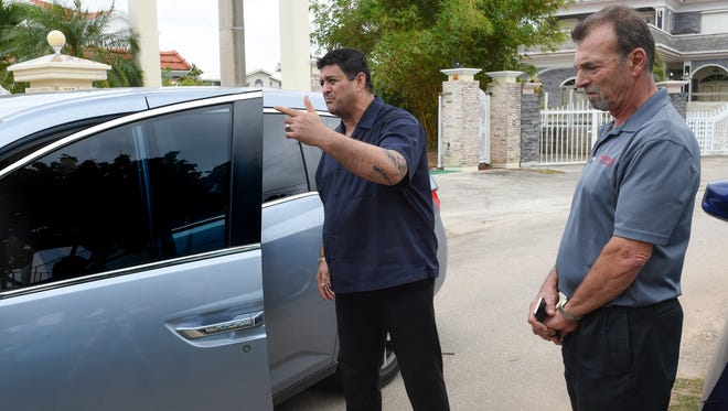 """Neighbors Gabriel Simon, right, and Alfredo Bustamante confront a neighborhood tenant about underground tourism on their in Tamuning street on Jan. 21. The pair suspects at least two underground bed-and-breakfasts are currently operating on their street. """"If you don't respect our culture and laws, as a local, then I have a problem,"""" said Bustamante."""