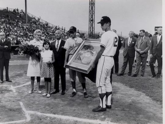 Bat boys present Morrie Silver with an aerial photo
