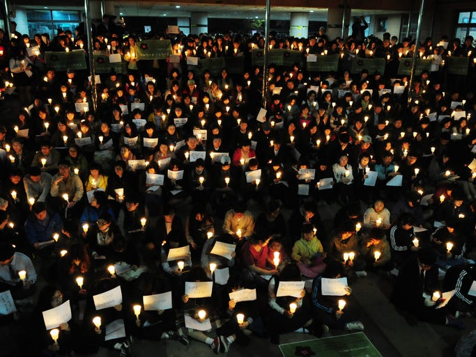 Family and schoolmates of missing passengers of the capsized ferry Sewol, hold candles during a vigil at Danwon High School in Ansan, South Korea on April 18.
