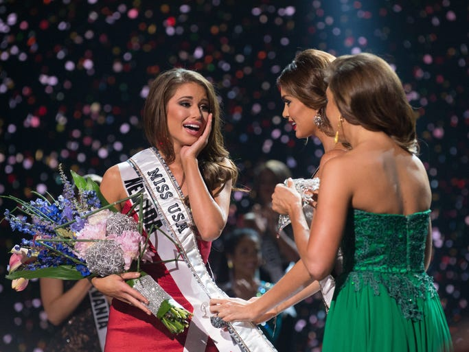 Nia Sanchez, Miss Nevada USA 2014, is congratulated by runner-up Audra Mari, Miss North Dakota USA, center, and former titleholder Erin Brady, Miss USA 2013, right, after she was announced as Miss USA at the end of the competition on June 8 from the Baton Rouge River Center.