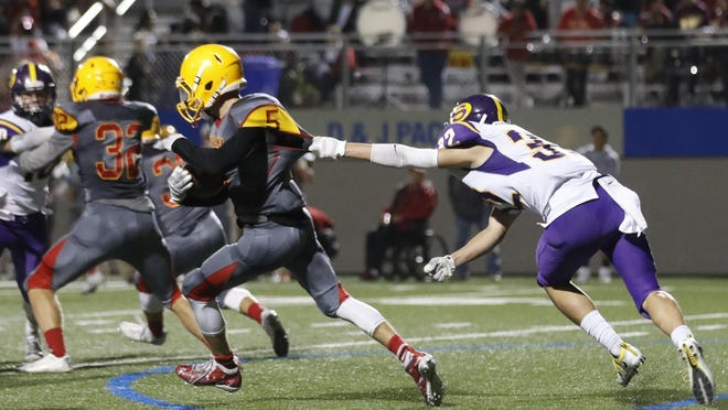 Salinas' Isaac Moreno (32) reaches for the jersey of Palma's Kevin Telford during their game Friday night.