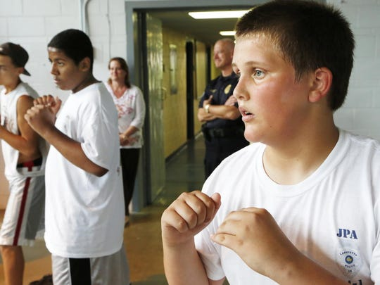 Following the direction of Officer Amanda Deckard, Drew DeBoer, 14, right, and other participants practice the self-defense movements of R.A.D. (Rape Aggression Defense) as Lafayette Police Department hosts its first Junior Police Academy Wednesday, July 16, 2014, at LPD's training center, 1301 South Street in Lafayette. The goal of the program is to inspire responsible citizenship, foster positive interaction with police officers and to teach young people about the challenges police face on a daily basis. DeBoer, who will be an eighth grade student at Lafayette Tecumseh Junior High in the fall, said he would like to pursue a career in law enforcement.