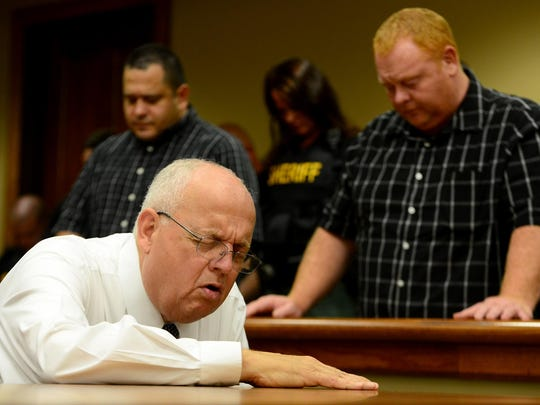 Cave Springs Baptist Church Pastor Ronnie Geary kneels in prayer as local law enforcement officers stand behind him during Tuesday's prayer service.