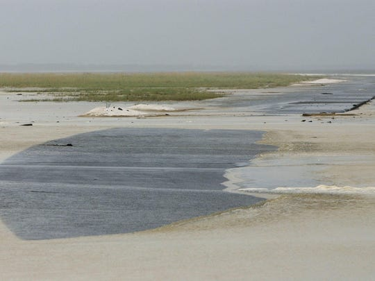 This file photo shows Fort Pickens Road breached as the sea builds from Hurricane Katrina. The proposed ferry service will offer visitors another option to access Fort Pickens.