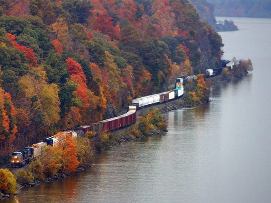 A freight train travels south seen from the Walkway Over the Hudson framed by the colors of fall in the background.