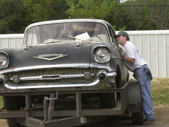 A man takes a closer look at a 1957 Chevy during a previous Ozarks Antique Auto Club Swap Meet.