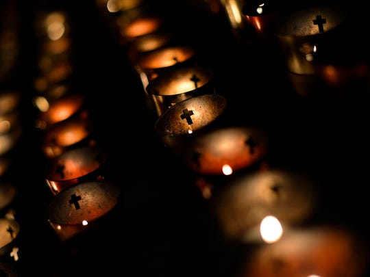 Candles illuminate crosses Friday in the Shrine of Our Lady of Good Help in Champion.