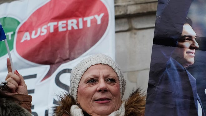 """A protester holds a poster with a picture of Greek Prime Minister Alexis Tsipras, right, during a rally to show solidarity with Greece in central London, Sunday, Feb. 15, 2015. Hundreds of protesters gathered in support of the new government and the anti-austerity movement in Greece. Greece's new left-wing government is pressing for a short-term """"bridge"""" agreement with eurozone lenders and a longer-term debt relief deal later this year."""