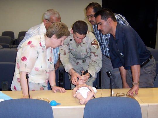 Capt. David Mathias teaches Iraqi health care providers how to resuscitate an infant.