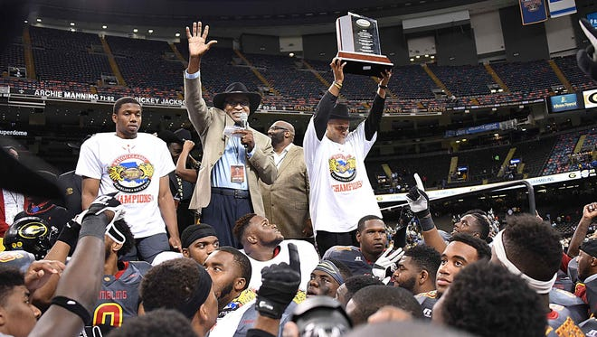 Grambling quarterback Johnathan Williams, left, and coach Broderick Fobbs, right, celebrate the Tigers' win over Southern in the 2015 Bayou Classic.