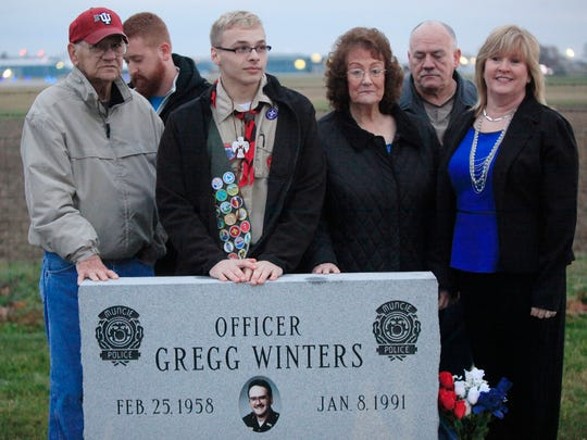 Survivors of slain Muncie police officer Gregg Winters stand with Aaron Waters, a Boy Scout who placed a monument at the site where Winters' patrol car came to rest after he was shot in December 1990.