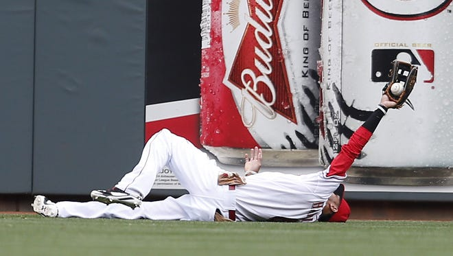 Cincinnati Reds center fielder Billy Hamilton (6) holds the ball up after a diving catch off the bat of Milwaukee Brewers center fielder Carlos Gomez (27) in the first inning.