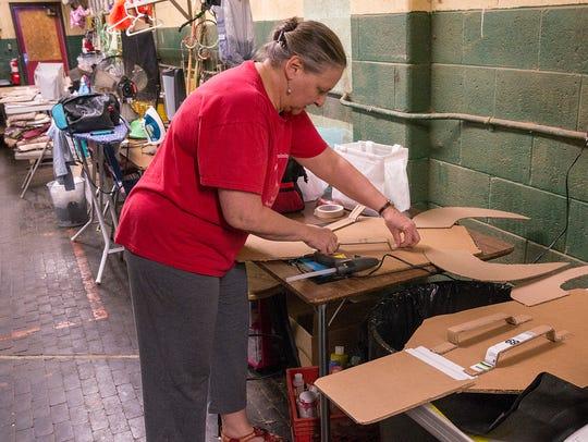 Nancy Koppin works on masks for the Lion King production