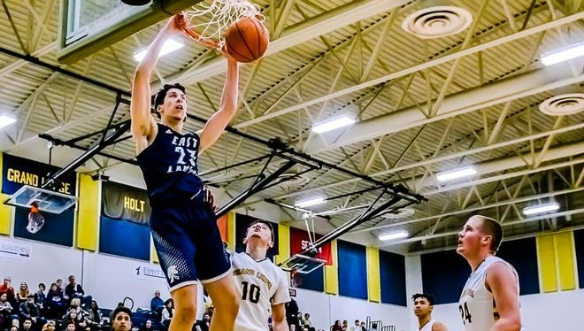 Brandon Johns ,top, of East Lansing dunks over Cam Collins ,10, of Grand Ledge to put East Lansing up 37-26 in the 3rd quarter of their game Tuesday Febryary 16, 2016 in Grand Ledge.