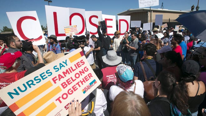 "A crowd gathers at the entrance to the ICE's El Paso Processing Center at Montana and Mattox on Tuesday, holding large letters that spell ""CLOSED."" The El Paso march protested the Trump administration's immigration policy separating families."