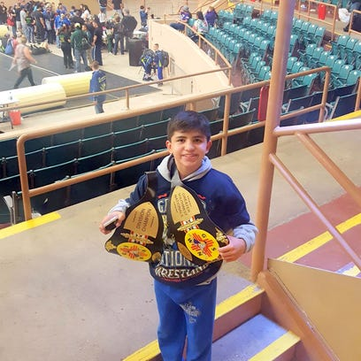Marcus Najera, 12, stands with his two national championships