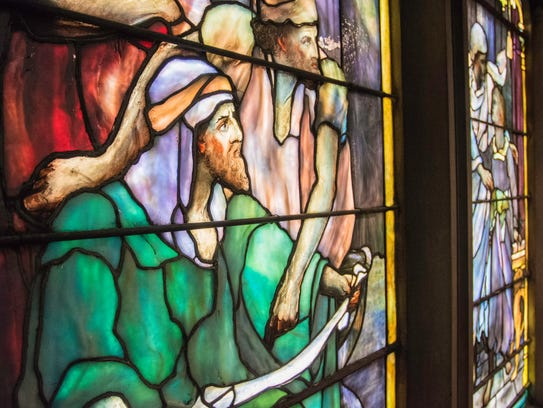 A large Tiffany stained glass window is seen in the