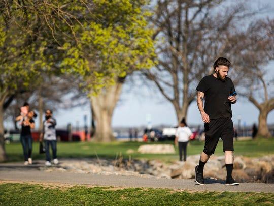 Sean Merritt walks through Battery Park as he plays Pokemon Go in New Castle.