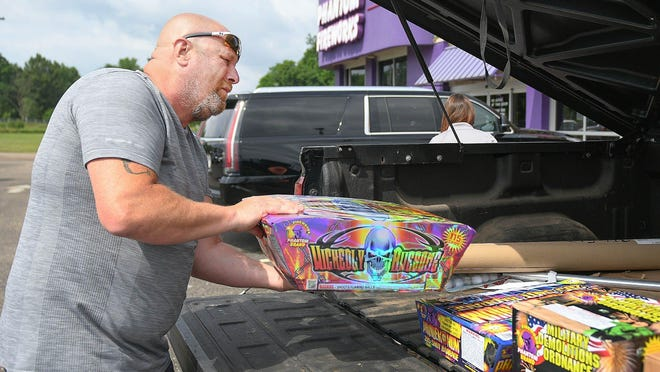 Aaron Schley, of Robertsville, loads the back of his truck with fireworks from Phantom Fireworks in Canton on Saturday. Schley said he was able to stay within his budget, but Phantom's sales and discounts gave him a bigger bang for his buck this year.