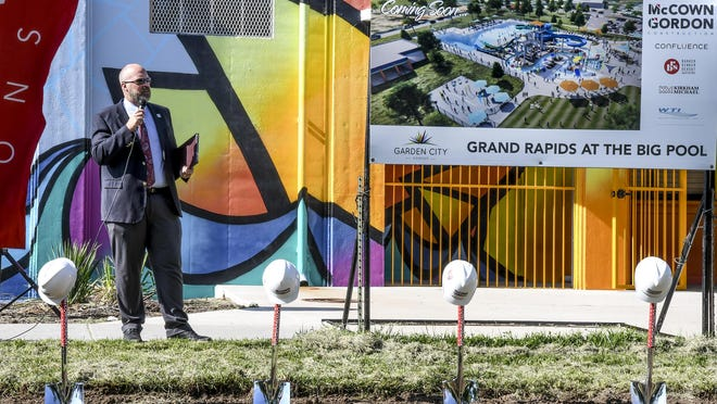 Garden City manager Matt Allen addresses those gathered for a groundbreaking ceremony for the Grand Rapids at The Big Pool project on July 23 beside a rendering of what the project could look like.