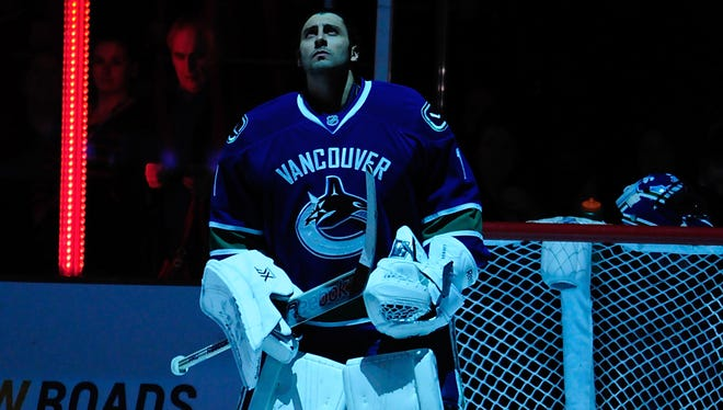 Vancouver Canucks goaltender Roberto Luongo stands in net before the start of the first period against the Winnipeg Jets.