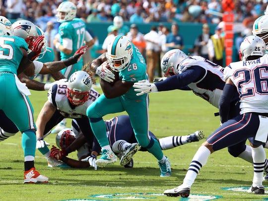 Jan 3, 2016; Miami Gardens, FL, USA; Miami Dolphins running back Lamar Miller (26) runs past New England Patriots defensive end Jabaal Sheard (93) during the first half at Sun Life Stadium. Mandatory Credit: Steve Mitchell-USA TODAY Sports