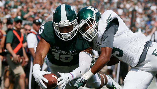 Michigan State wide receiver AJ Troup leaps into the end zone past Eastern Michigan's Jason Beck on Sept. 20, 2014.