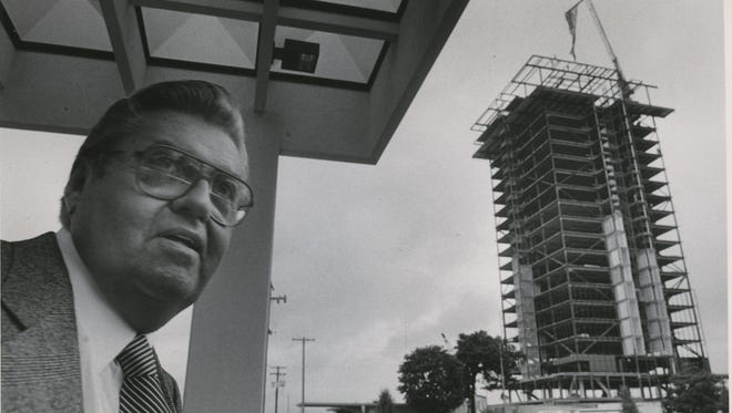 John Q. Hammons stands in front of Hammons Tower while it was being constructed in 1985.