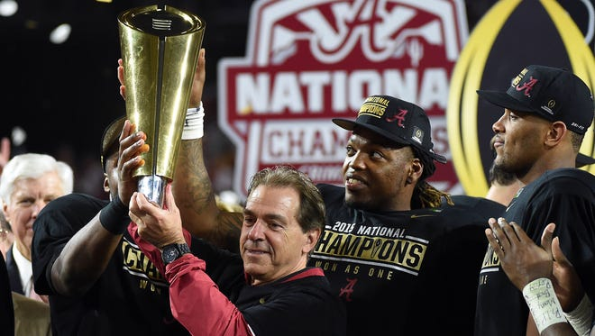 Alabama Crimson Tide head coach Nick Saban and running back Derrick Henry (2) celebrate with the 2016 CFP National Championship trophy after beating the Clemson Tigers at University of Phoenix Stadium.