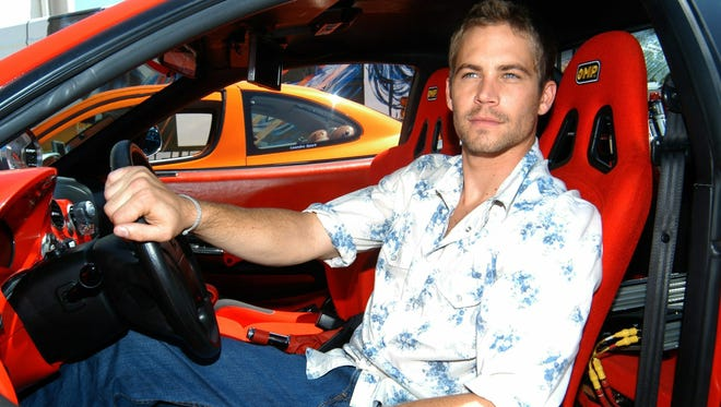 Paul Walker poses in a car to promote his '2 Fast 2 Furious' in Madrid, Spain, in June 2013.