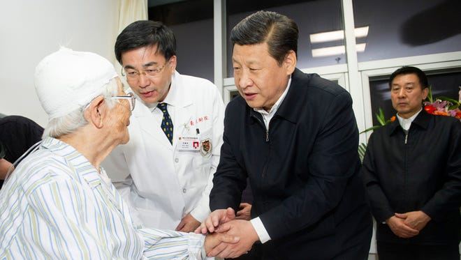 In this photo released by China's Xinhua News Agency, Chinese President Xi Jinping, center, visits a patient at the Huangdao branch of the hospital affiliated with the Medical College of Qingdao University in Qingdao, a coastal city in east China's Shandong Province on Sunday.