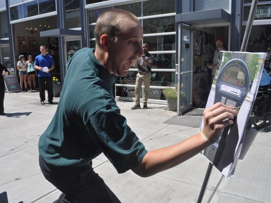 Alex Remizowski, who works in the accounting department for Tompkins Trust Company, finishes a workday relay race by paying a parking meter.