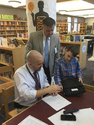 Freedom Middle School assistant principal Adam Demonbreun distributes a Chromebook to 7th grade student Tobey Stokes. FSSD superintendent David Snowden oversees the exchange.
