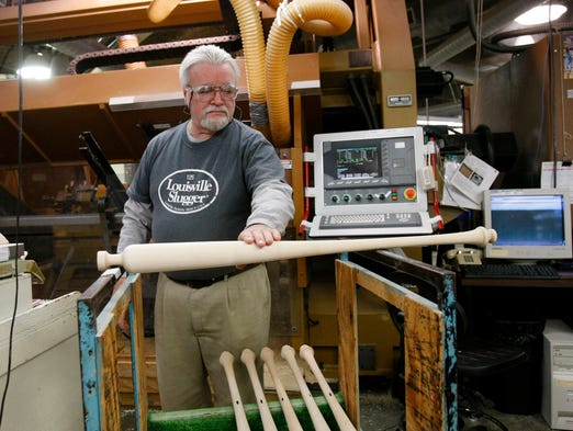 Louisville Slugger employee Danny Luckett rolls a professional player's bat along two straight edges to confirm its straightness at the Louisville Slugger Museum & Factory in Louisville, Ky.