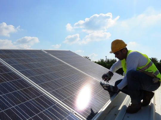 A worker installing a rooftop solar system.