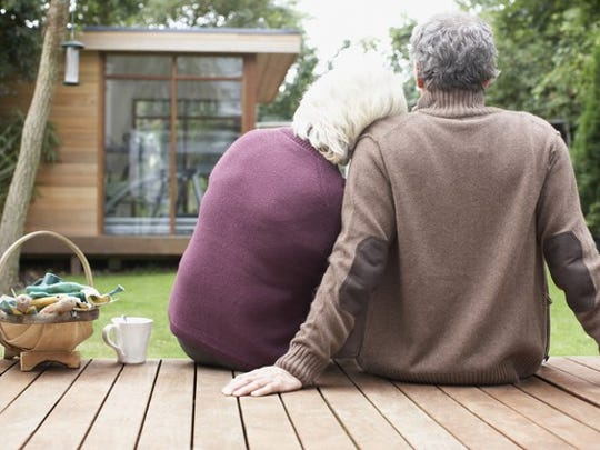 Older Couple Sitting On Wood Deck