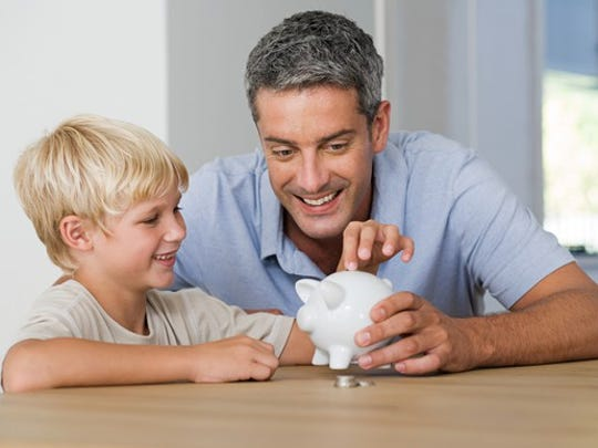 Father and son placing coins in a piggy bank.
