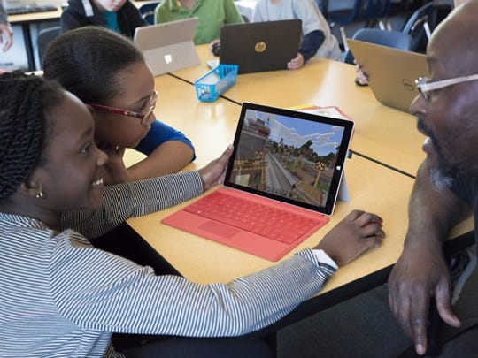 Two girls playing Minecraft on a Microsoft Surface