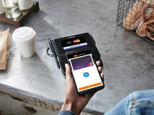 Consumer using MastePass at a sales checkout at a store.