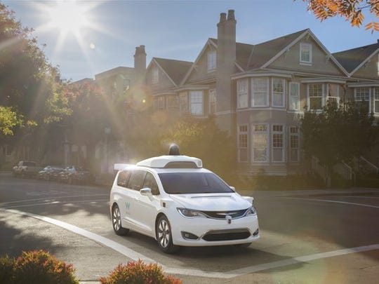 A white Chrysler minivan equipped with Waymo's self-driving system on a suburban street