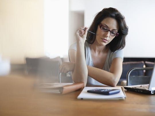 Woman sitting at table with notebook and calculator