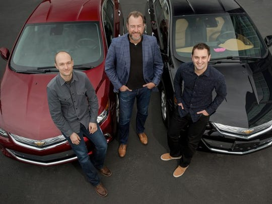 Green, Ammann, and Zimmer with two Chevrolet Volt plug-in hybrid sedans.