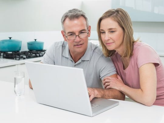 Couple looking at a computer screen together.