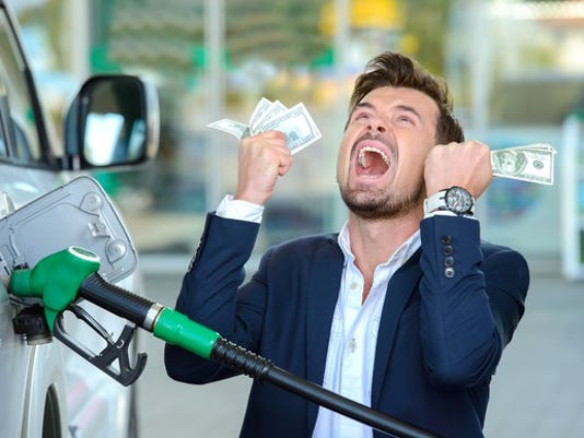 emotional-businessman-counting-money-with-gasoline-refueling-car-at-fuel-station_large.jpg
