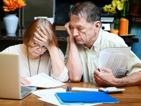 senior-couple-worried-looking-at-bills-finances-debt_large.jpg