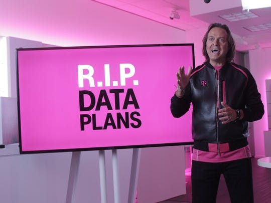 "T-Mobile CEO John Legere standing in front of a sign that says ""R.I.P. Data Plans"""